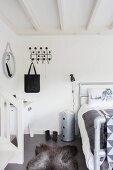 Schlafzimmer mit Tierfellvorleger auf grauem Boden, an weißer Wand schwarze Klassiker-Garderobe