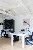 Weisser Schreibtisch und schwarze Klassiker-Schalenstühle vor schwarzem Regal mit Ablagetisch
