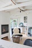Blick über Schreibtisch auf schwarzen Sessel mit weissem Schaffell und Beistelltisch mit Drahtgestell vor Kaminfeuer
