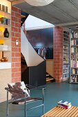 Staircase in industrial loft apartment with brick walls and concrete ceiling