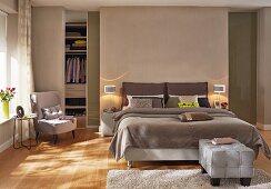 Box-spring bed in front of walk-in wardrobe in elegant bedroom