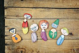 Pebbles painted as whimsical characters on rustic wooden surface