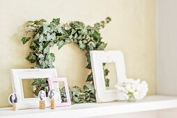 Ivy wreath, vintage picture frames and place cards hand-made from portraits stuck on corks on floating shelf