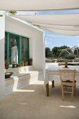 Mediterraner Hof mit Sonnensegel und Tisch