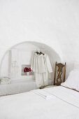 Clothes rail in arched niche in bedroom