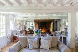 Ländliches Wohnzimmer mit Balkendecke und offenem Kamin