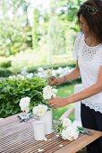 Frau steckt frisch geschnittene weiße Rosen in weiße Vase