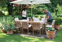 Gartensitzplatz mit Sonnenschirm, Frau und Mann beim Tischdecken