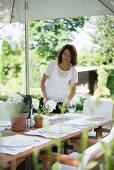 Frau beim Dekorieren des gedeckten Gartentisches