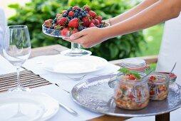 Hände halte Glasschale mit frischen Beeren und Tablett mit Einmachgläsern auf Gartentisch