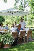 Gäste an gedecktem Tisch mit Sonnenschirm im Garten