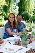 Paar an gedecktem Tisch im Garten mit Glaskrug