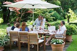 Gartenfeier mit Gästen an gedecktem Tisch mit integriertem Sonnenschirm