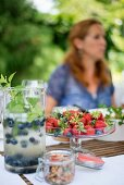 Refreshing drink with blueberries in carafe and fresh strawberries in glass dish on garden table