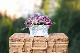 Arrangement of pink flower in china bowl on wicker trunk