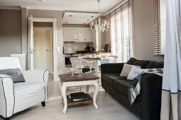 Comfortable upholstered furniture in lounge area in front of elegant, fitted country-house-style kitchen