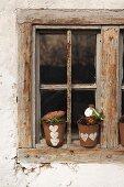 Selbstgestaltete winterliche Blumentöpfe mit Herzmotiv auf Fensterbrett