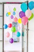 Colourful balloons tied to door frame and door