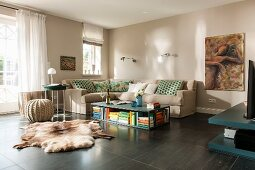 Comfortable lounge area with beige walls, corner sofa, coffee table and animal-skin rugs on dark floor