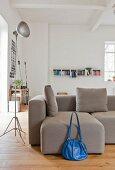 Blaue Tasche vor grauem Sofa in urbanem Loft