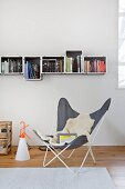 Butterfly chair below bookcase made from plastic crates
