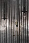 Three pendant lamps with minimalist wire lampshades in front of shiny corrugated metal background