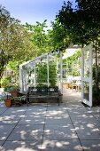 White-framed greenhouse on paved terrace