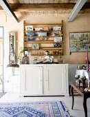 Buddha figurine on white cabinet below books on wooden shelves in rustic interior