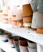 Various stacked terracotta pots on white shelf