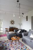 Retro Beistelltisch und graue Polstermöbel in schlichtem Wohnraum, Pendelleuchten mit sichtbaren Leuchtmitteln an weißer Holzbalkendecke