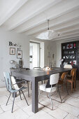 Various retro chairs around grey table in dining room with white wood-beamed ceiling