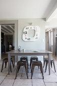 Klassiker Metallhocker um grauen Holztisch vor Wanddekoration und Durchgängen, heller Fliesenboden in restauriertem Altbau