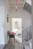 Treppenhaus mit grauem Stuhl vor offener Zimmertür und Blick auf Bett in restauriertem Ambiente