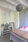 Blick über Bett mit Tagesdecke auf nostaglisches Schülerpult in renoviertem Schlafzimmer