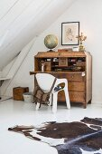 Cowhide rug on white floor and white shell chair at antique wooden bureau with globe on top in attic room