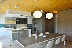 Long table in dining area and glass partition wall with view of kitchen