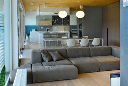 Comfortable sofa in open-plan designer living area with view of kitchen through glass partition wall