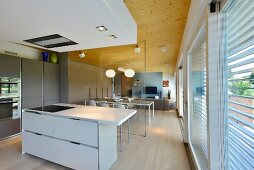 View from kitchen through glass partition wall into open-plan living area with wooden ceiling