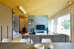 View from dining area into open-plan designer living area with TV against pastel-blue wall