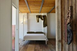 Modern four-poster bed in bedroom with old wooden floor