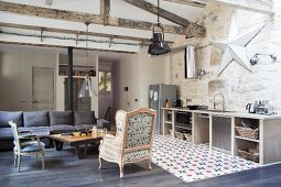 Antique armchair and chair around coffee table, dark grey sofa and kitchen counter in open-plan interior