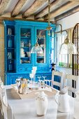 View across dining table below vintage pendant lamp to dresser painted bright blue in rustic dining room