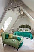 Antike Recamiere mit grünem Polsterbezug vor Doppelbett mit geschwungenem Kopfteil und dunkelgrüner Tagesdecke im Dachgeschoss