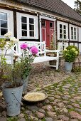 Zinc bucket of dahlias and bird bath on cobbles in front of white-painted garden bench and half-timbered house
