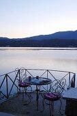 Romantischer Sitzplatz am See in der Abenddämmerung