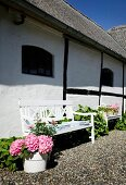 White-painted bench and flowering hydrangeas outside country house with exposed half-timber beams