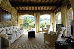 Mediterranes Wohnzimmer mit Steinwand und Panoramafenstern