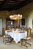 Mediterranes Esszimmer mit antiken Möbeln und Natursteinwand