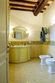 Klassisches Badezimmer mit gelben Fliesen und Holzdecke