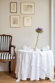 Baroque chair next to table with floor-length white tablecloth